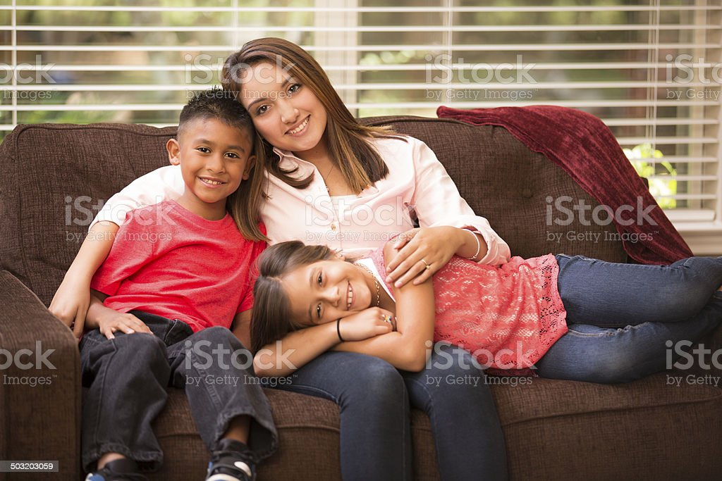 Hispanic mother and two children relaxing at home. stock photo