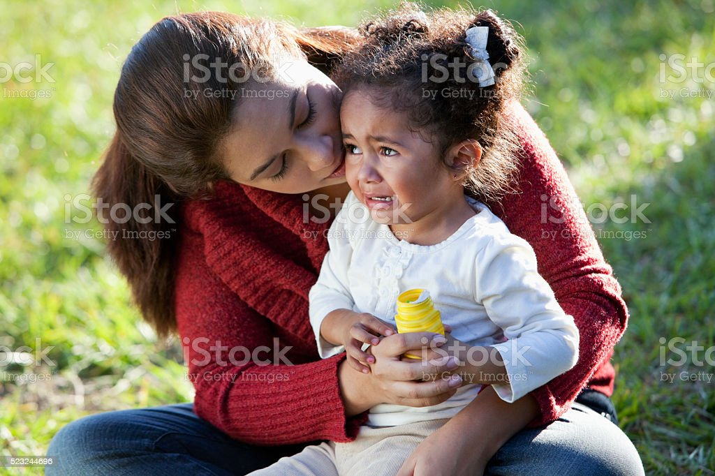 Hispanic mother comforting crying daughter stock photo