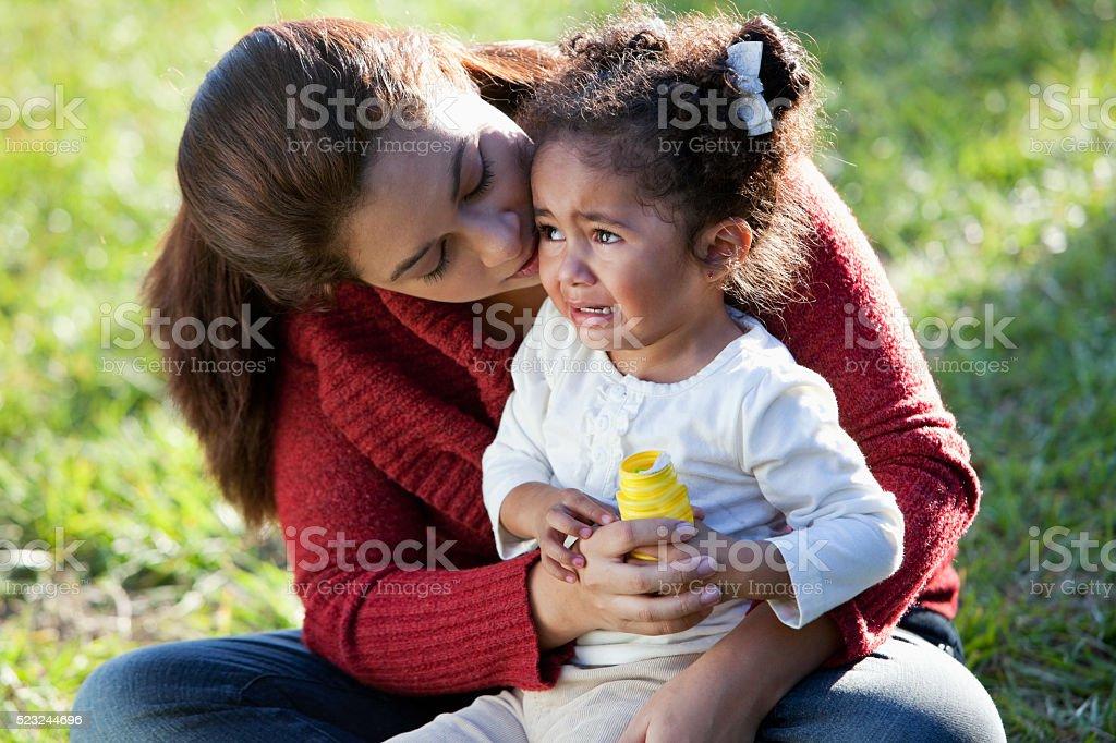 Hispanic mother comforting crying daughter stock photo