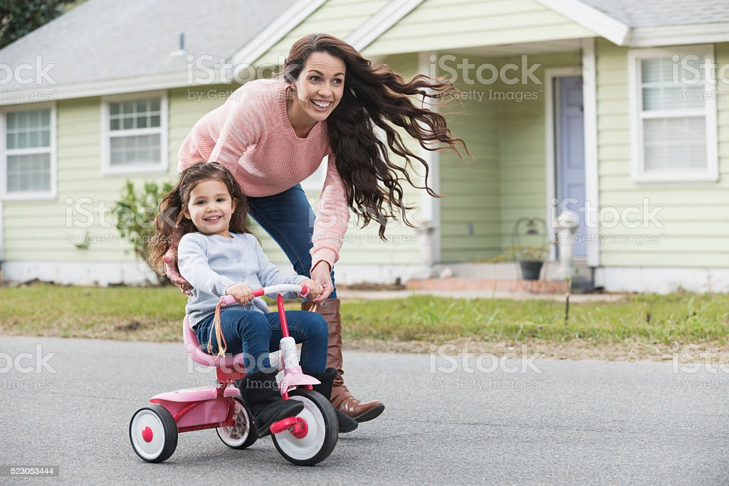 Hispanic mother helping daughter ride tricycle stock photo