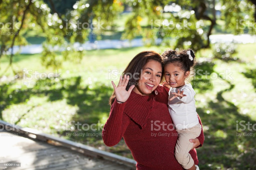 Hispanic mother holding little girl waving stock photo