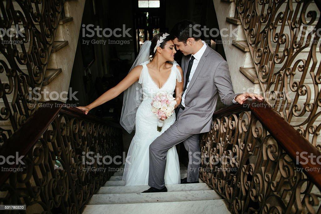 Hispanic newlywed couple flirting on a stairway stock photo