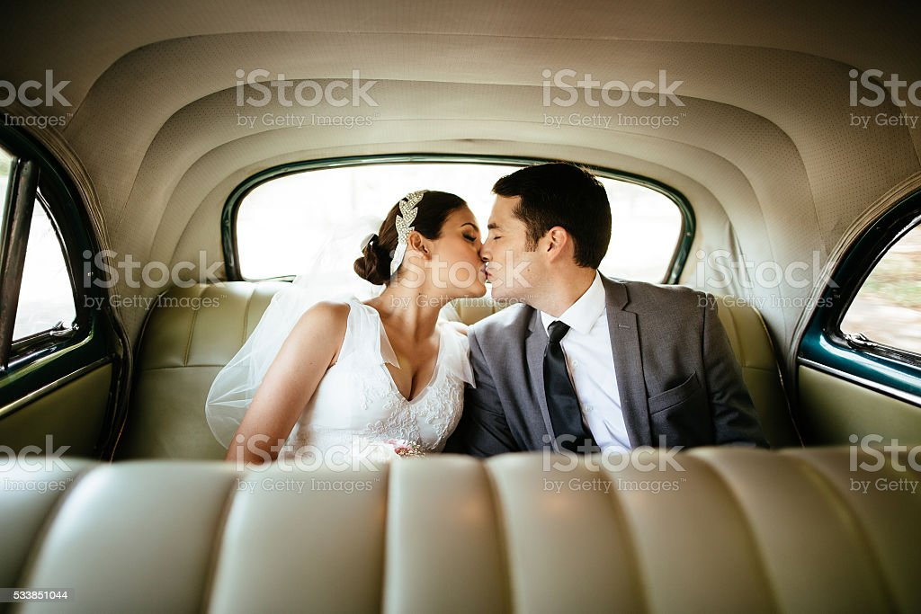 Hispanic newlyweds kissing in the backseat stock photo