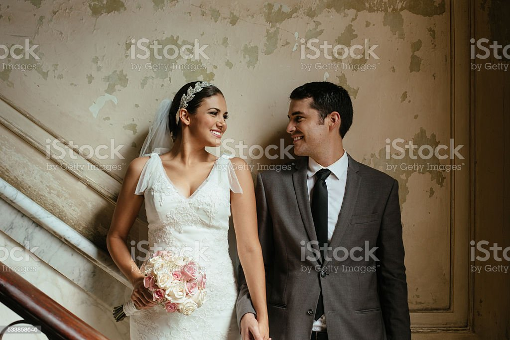 Hispanic newlyweds standing against a grunge wall stock photo