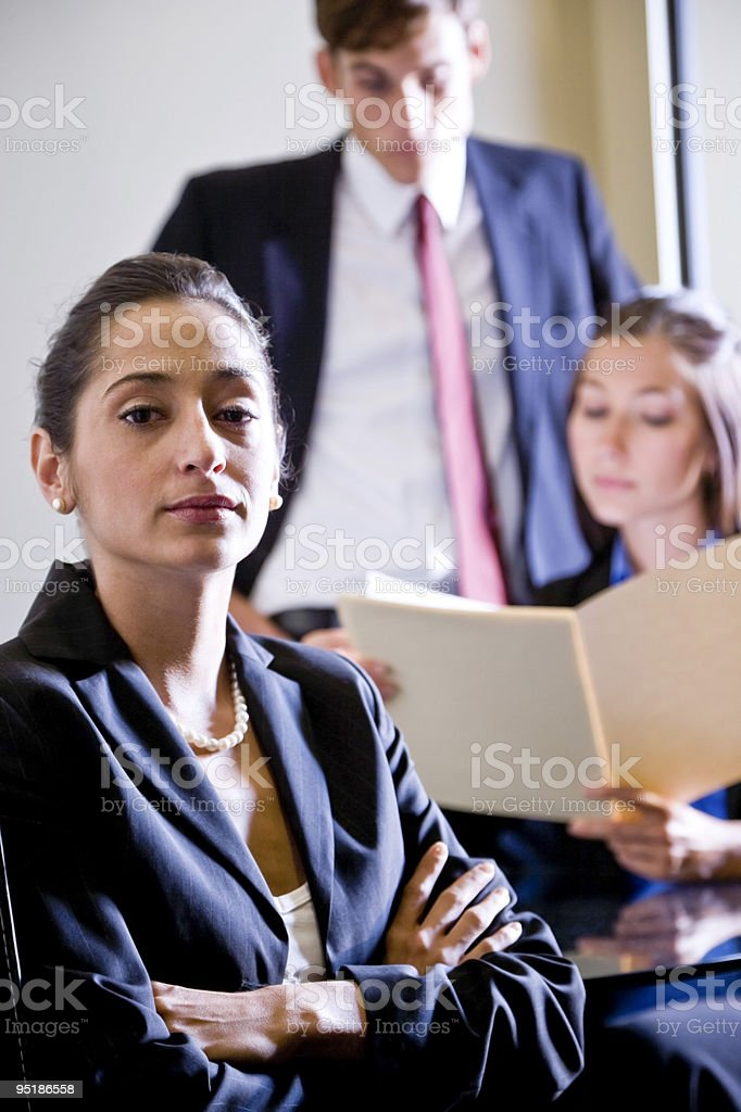Hispanic Empleada de oficina con colegas en fondo foto de stock libre de derechos