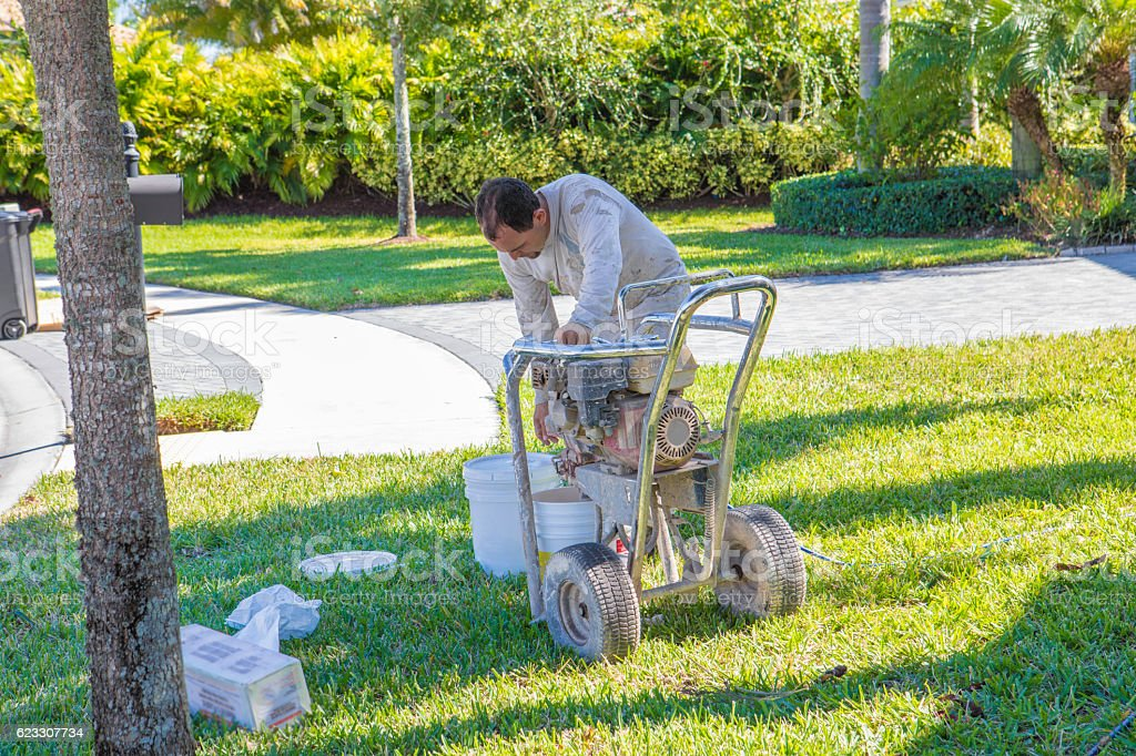 Hispanic painter refilling paint bucket for airless paint sprayer stock photo