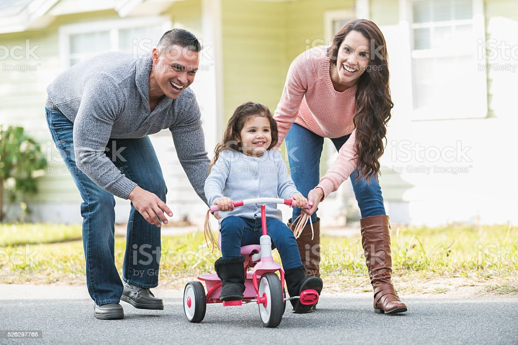 Hispanic parents helping girl ride tricycle stock photo