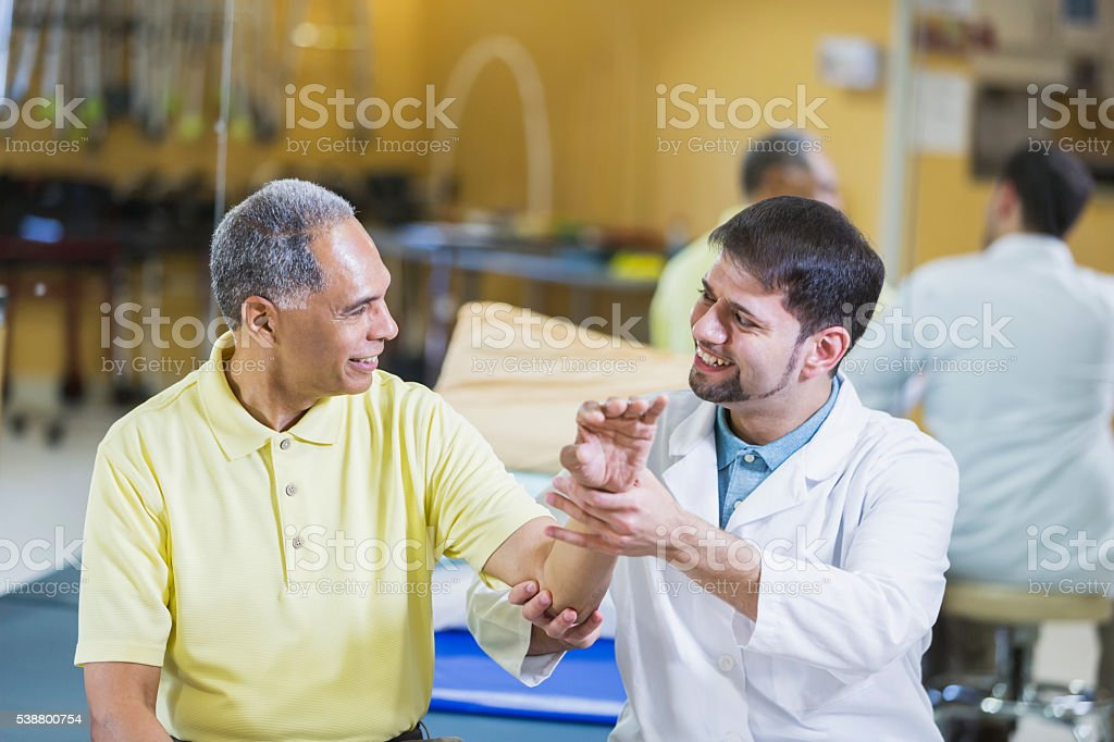 Hispanic physical therapist, African American patient stock photo