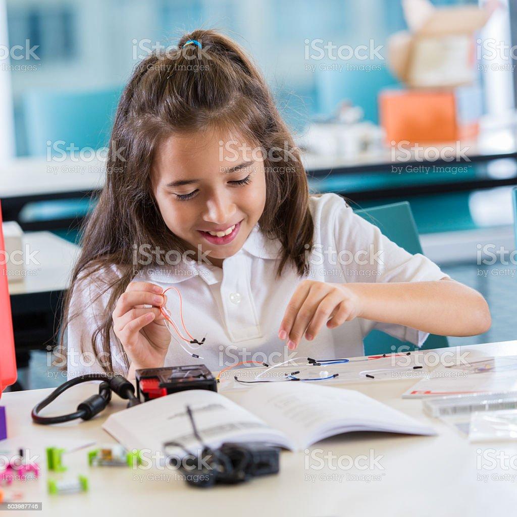 Hispanic private elementary school student using robotics kit stock photo