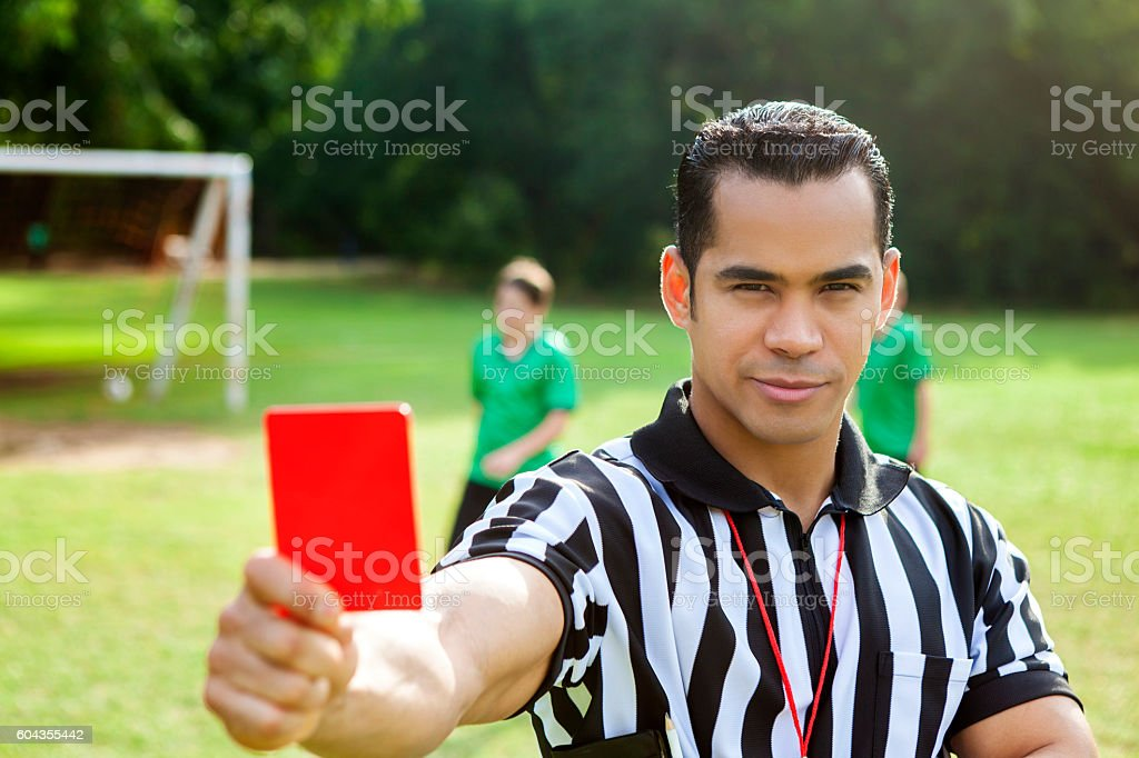 Hispanic referee holds a red penalty card during soccer game stock photo