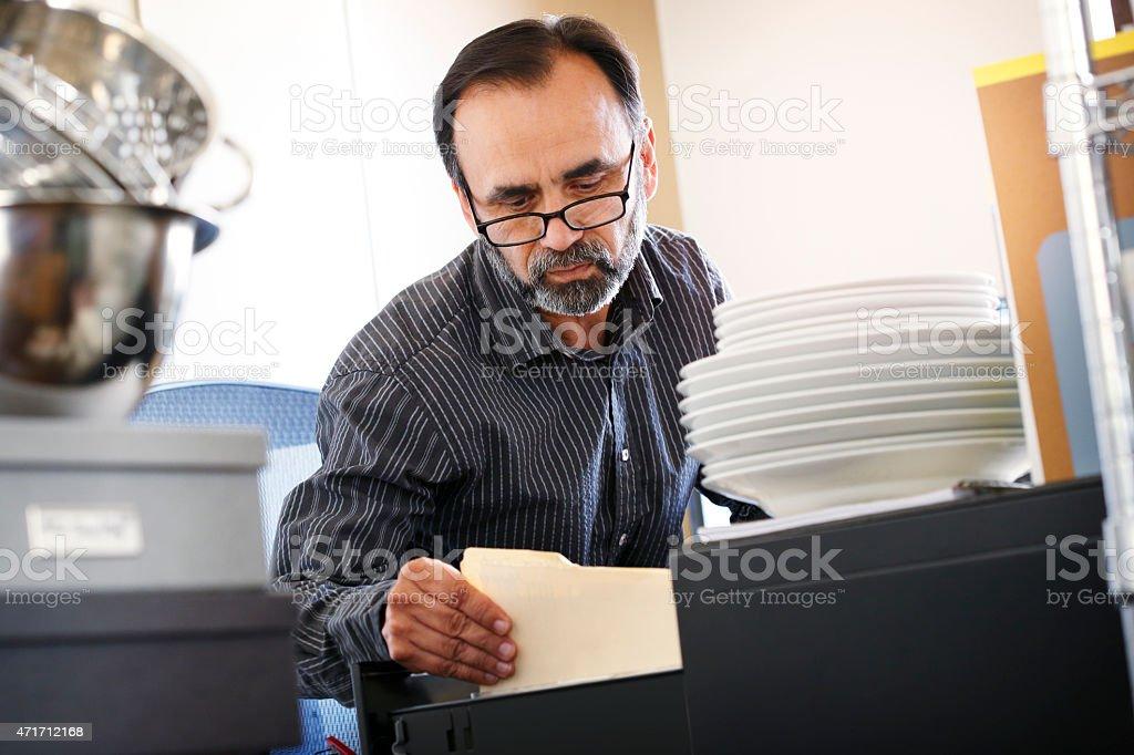 Hispanic restaurateur looking through file cabinet stock photo