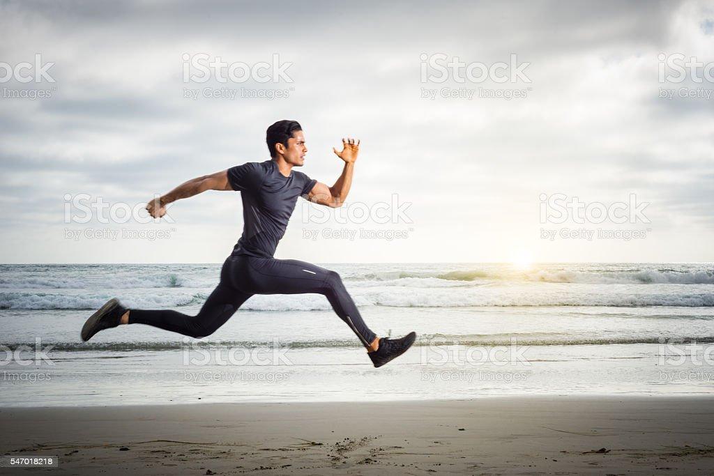 Hispanic Runner On The Beach stock photo