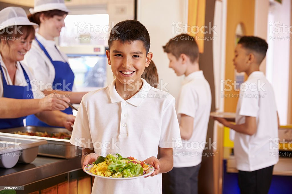 Hispanic schoolboy holds a plate of food in school cafeteria stock photo
