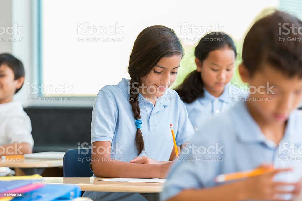 Hispanic schoolgirl concentrates while working on class assignment stock photo