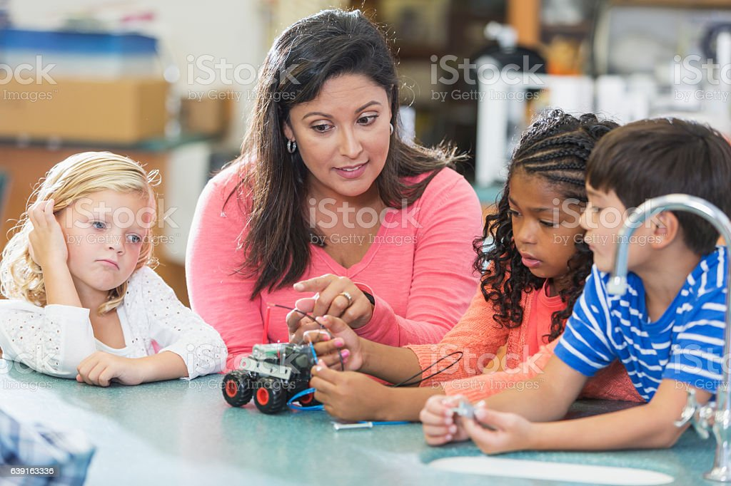 Hispanic science teacher teaching elementary school stock photo
