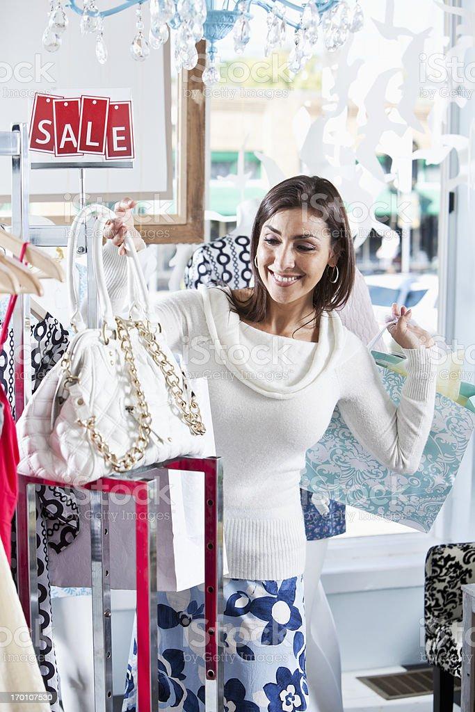 Hispanic shopper in boutique admiring handbag stock photo