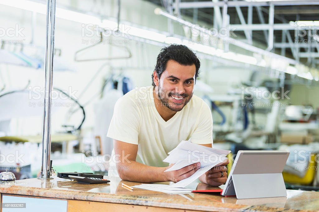 Hispanic small business owner, dry cleaner paying bills stock photo
