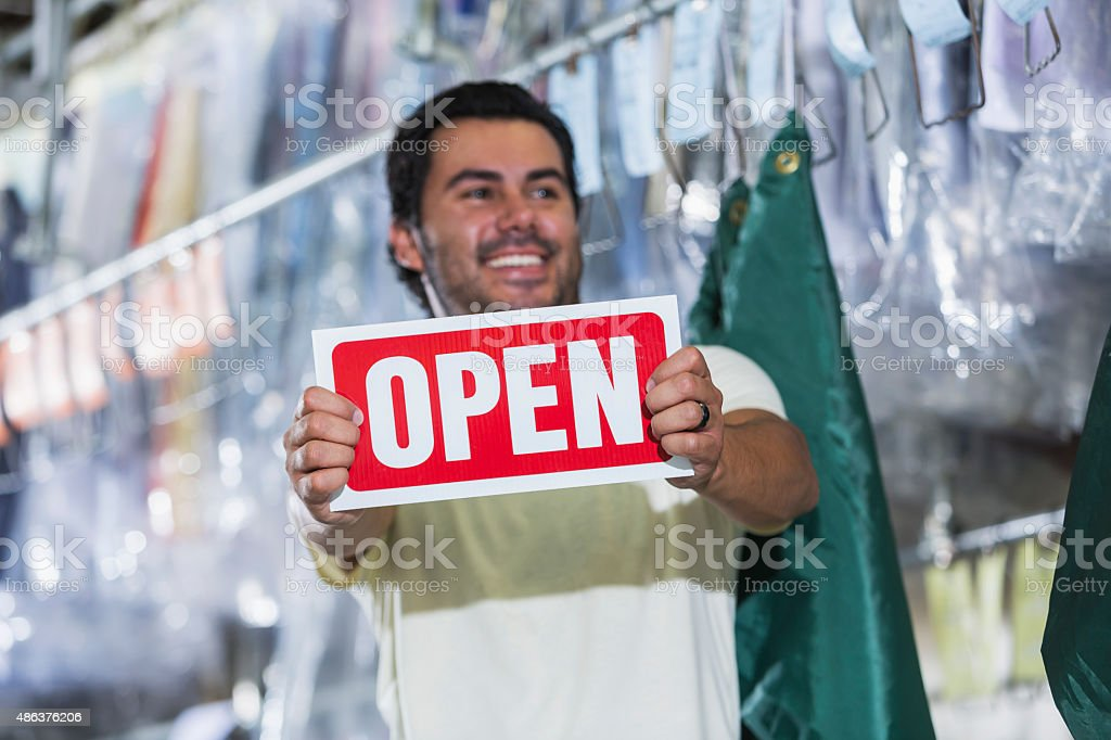 Hispanic small business owner of dry cleaners stock photo
