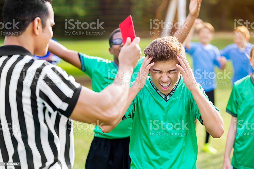 Hispanic soccer player yells while being shown red card stock photo