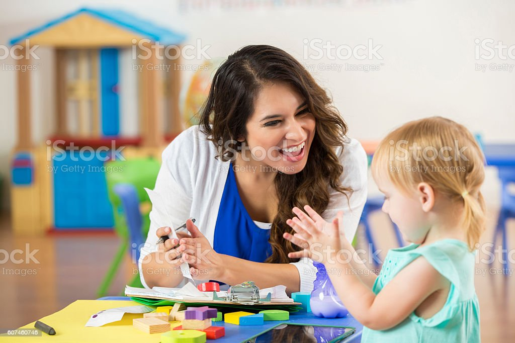 Hispanic teacher praises cute preschooler in daycare classroom stock photo