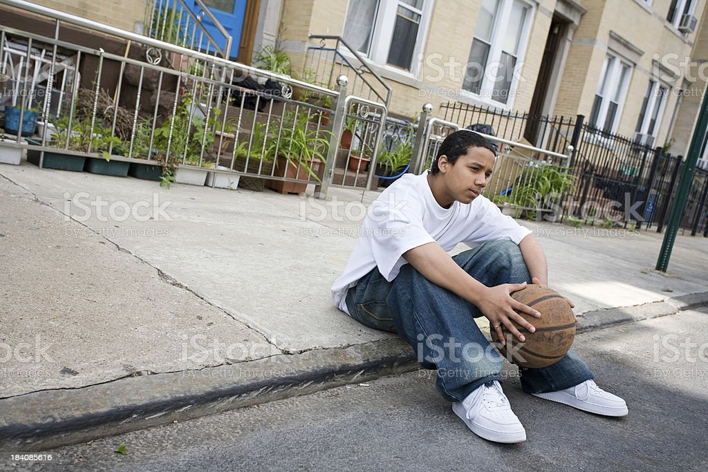 Hispanic teen sitting on the sidewalk royalty-free stock photo