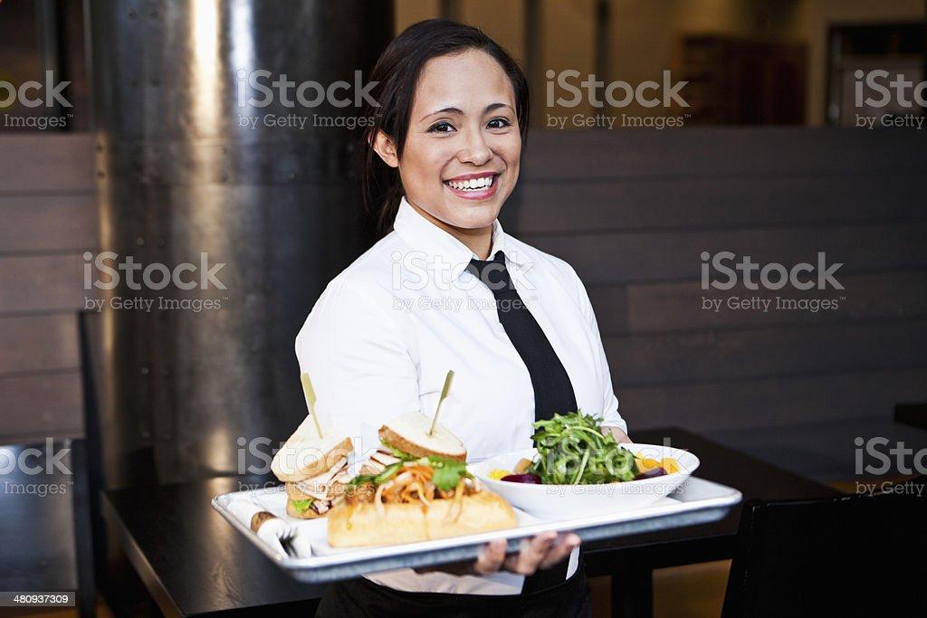 Hispanic waitress carrying tray of food stock photo