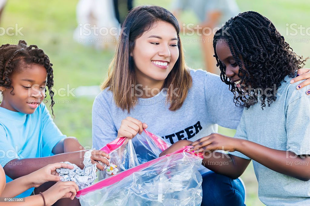 Hispanic woman and African American girls help with community cleanup stock photo