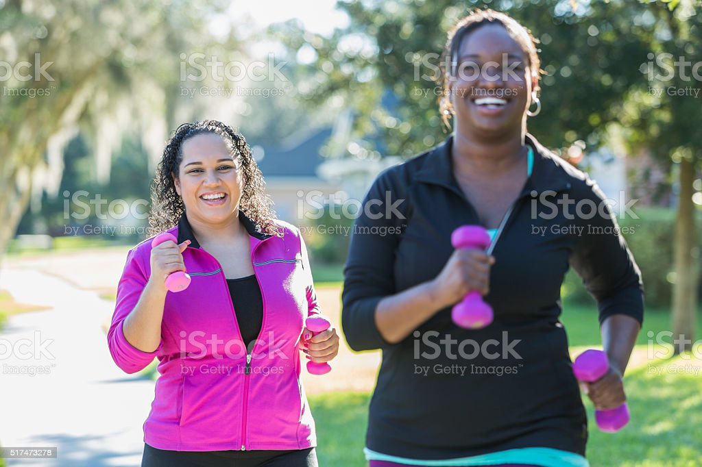 Hispanic woman and friend running with dumbbells stock photo