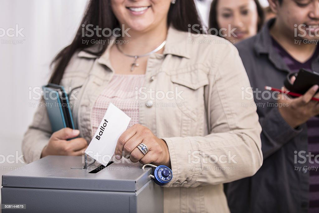 Hispanic woman casts ballot. Government election. Voters background. stock photo