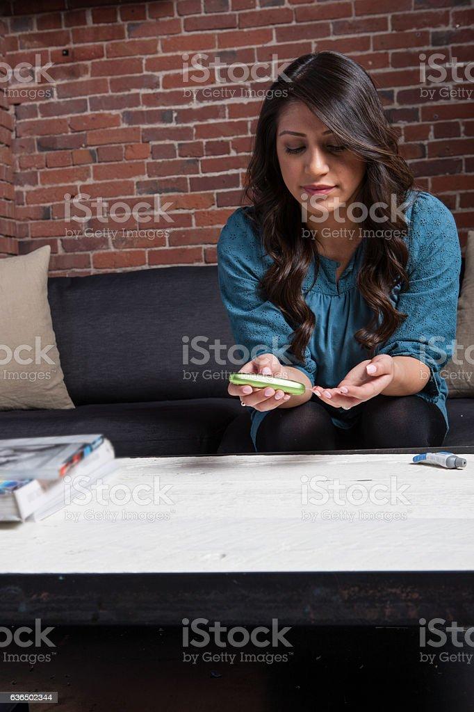 Hispanic Woman Checks Her Blood Sugar stock photo