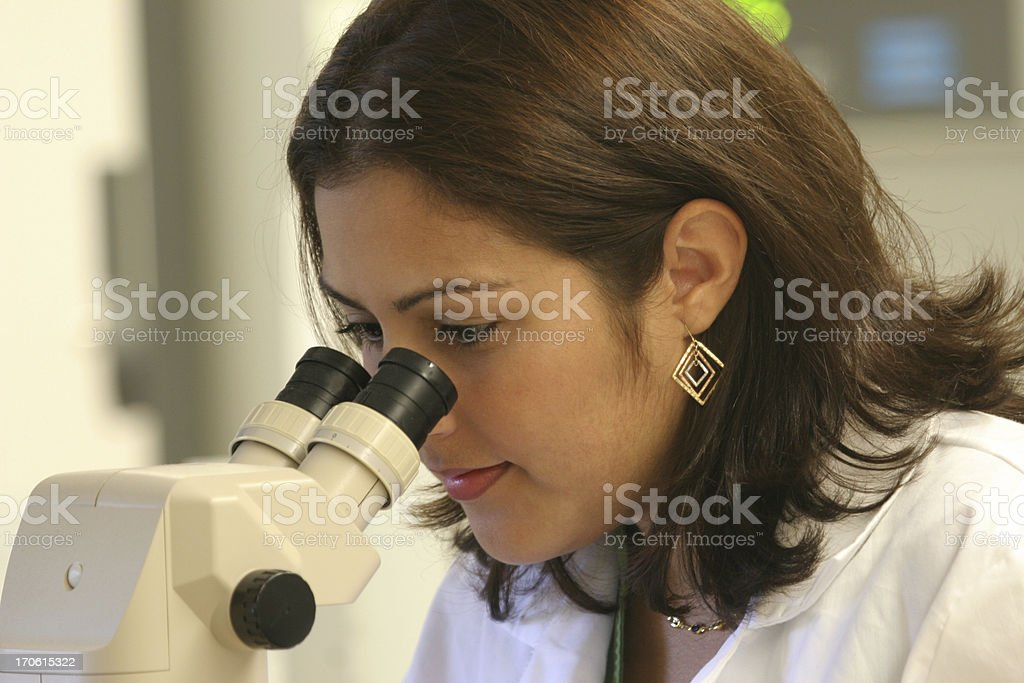 Hispanic Woman Doing Research Looking Through A Microscope royalty-free stock photo