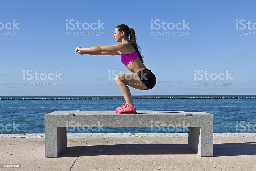 Hispanic woman doing squats by the water stock photo