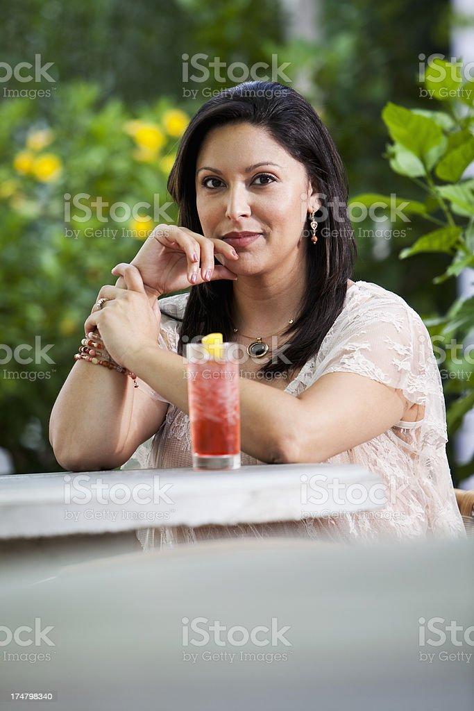 Hispanic woman drinking outdoors stock photo