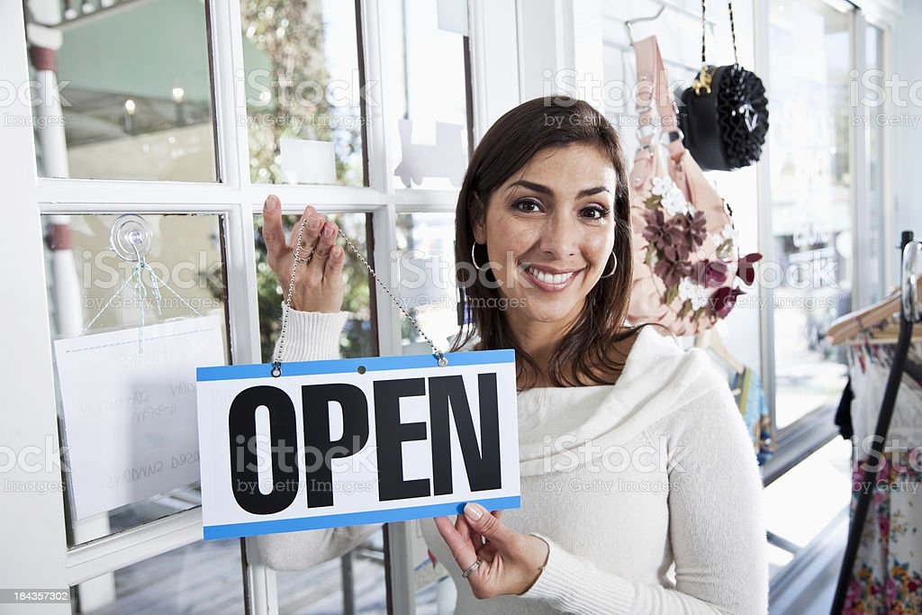 Hispanic woman in boutique with a open sign stock photo