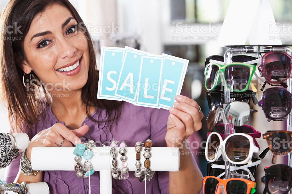 Hispanic woman in boutique with a sale sign stock photo