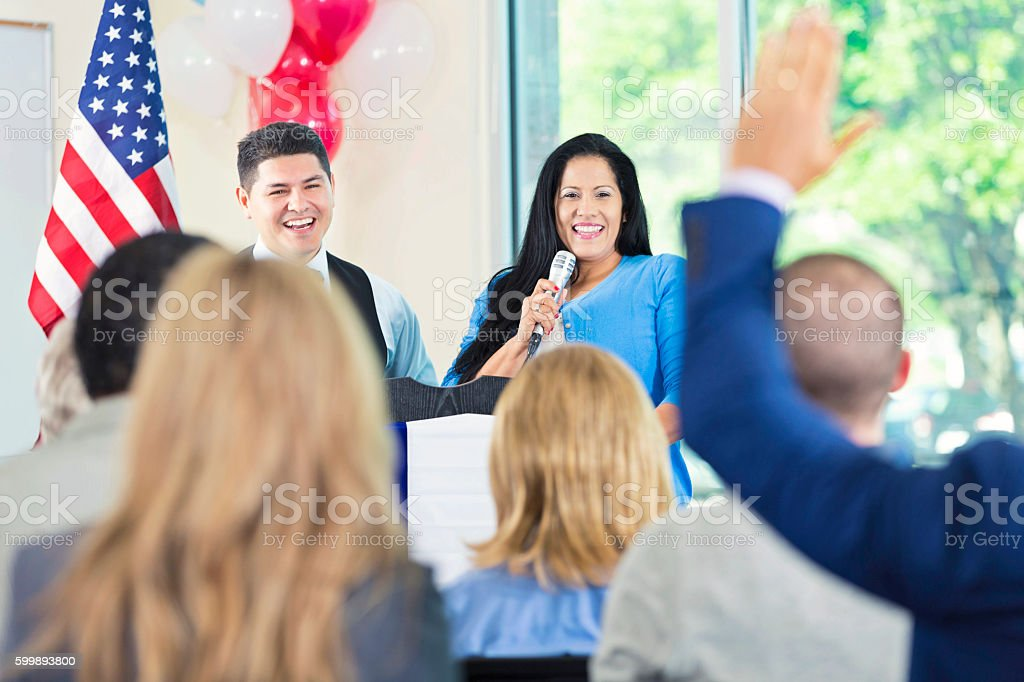 Hispanic woman introducing local government official during speech stock photo