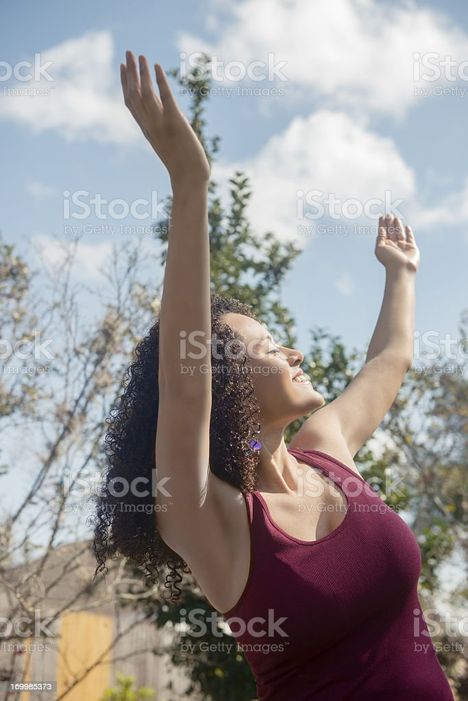 Hispanic Woman Lifts Arms to the Sky royalty-free stock photo