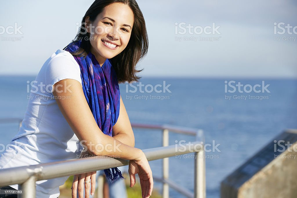 Hispanic Woman Looking Over Railing At Sea stock photo