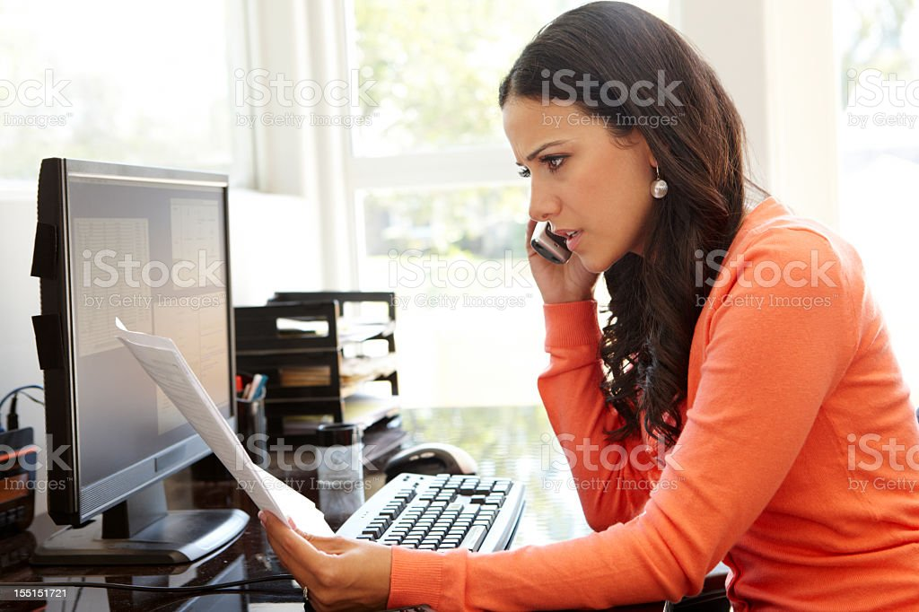 Hispanic woman on the phone with documents in home office stock photo