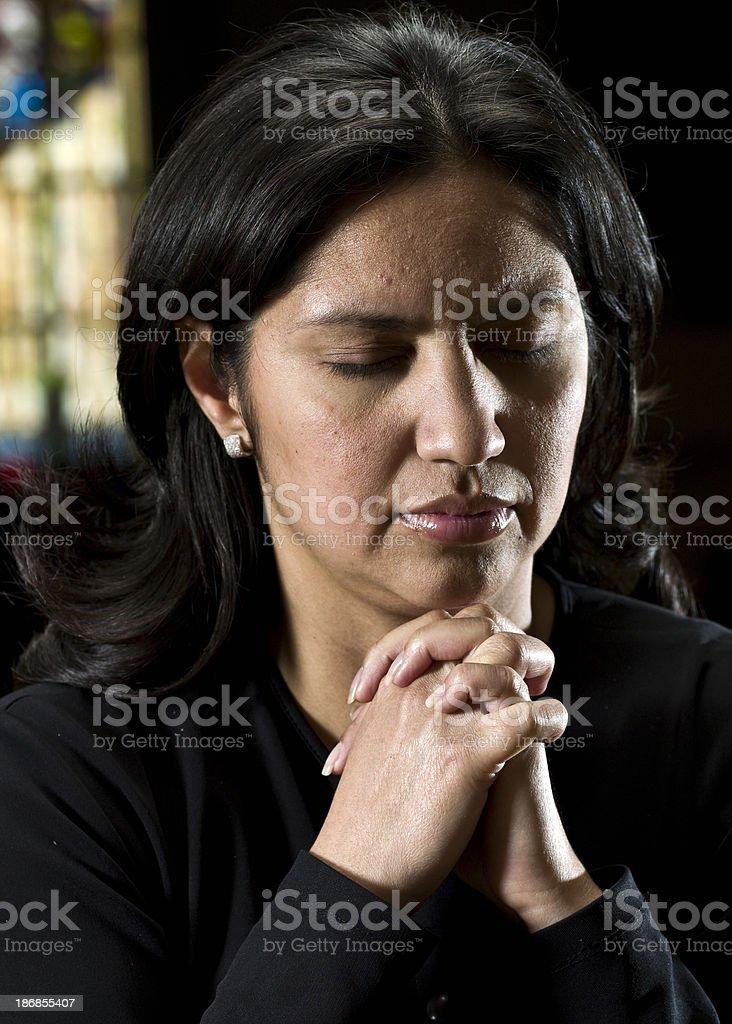 Hispanic woman praying at the church royalty-free stock photo