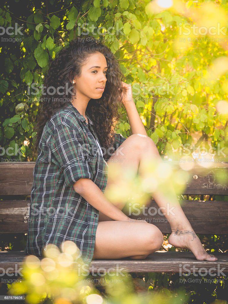 Hispanic woman sitting on a bench in a park stock photo