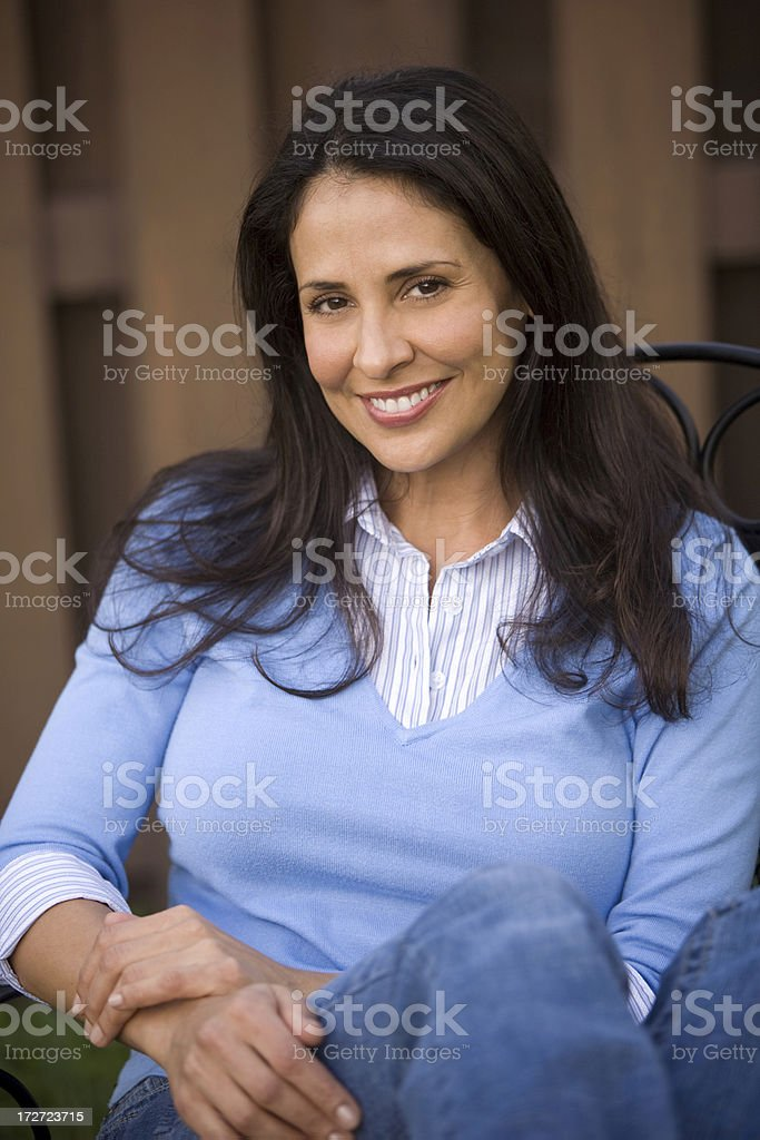 Hispanic woman sitting on a chair in back yard royalty-free stock photo