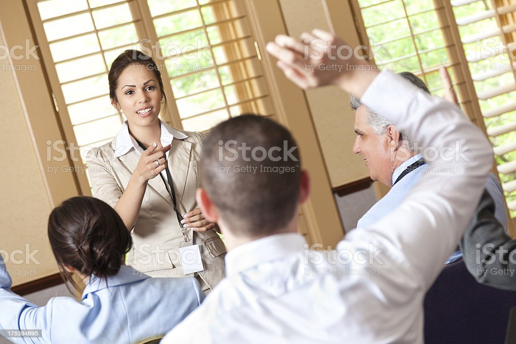 Hispanic woman speaking to a group of professionals royalty-free stock photo