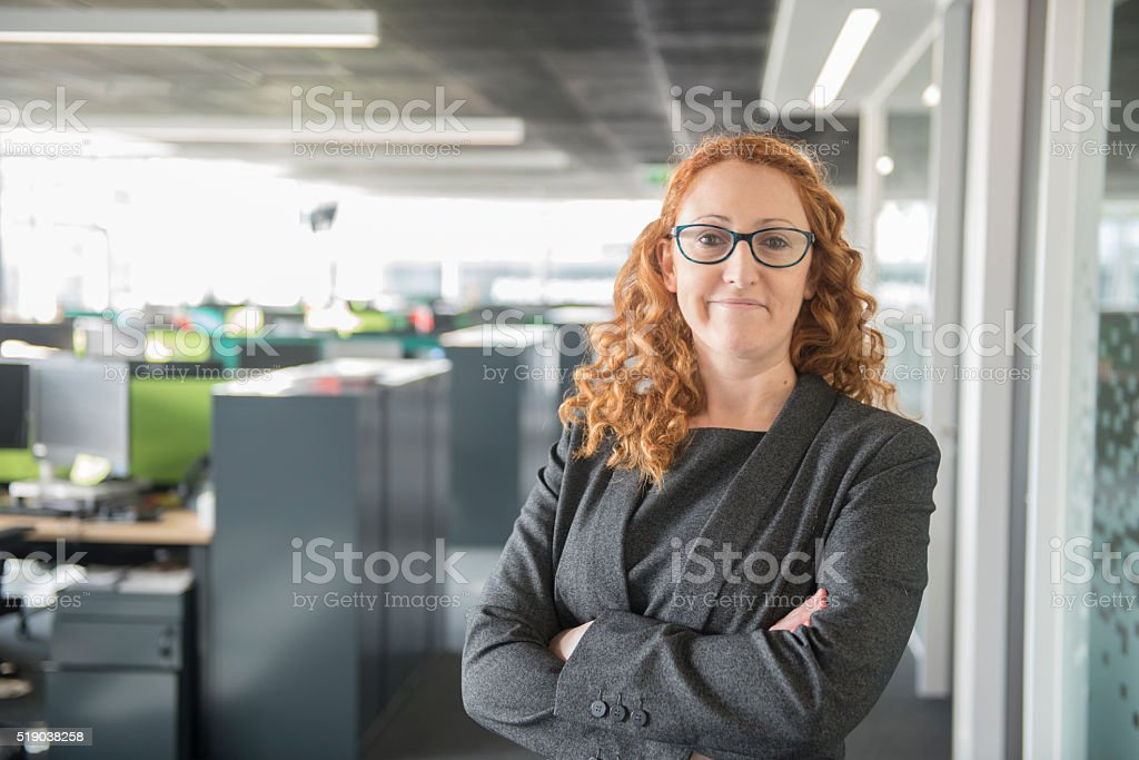 Hispanic woman standing in Office stock photo