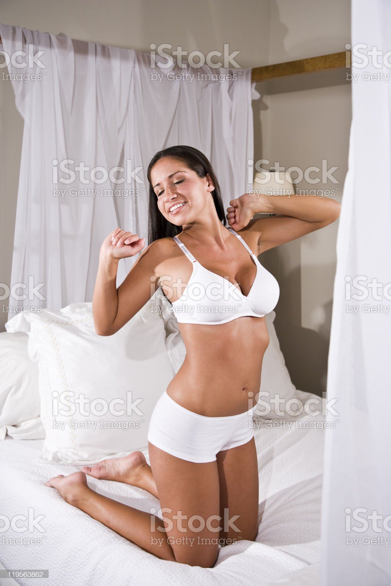 Hispanic woman stretching in bed wearing underwear royalty-free stock photo