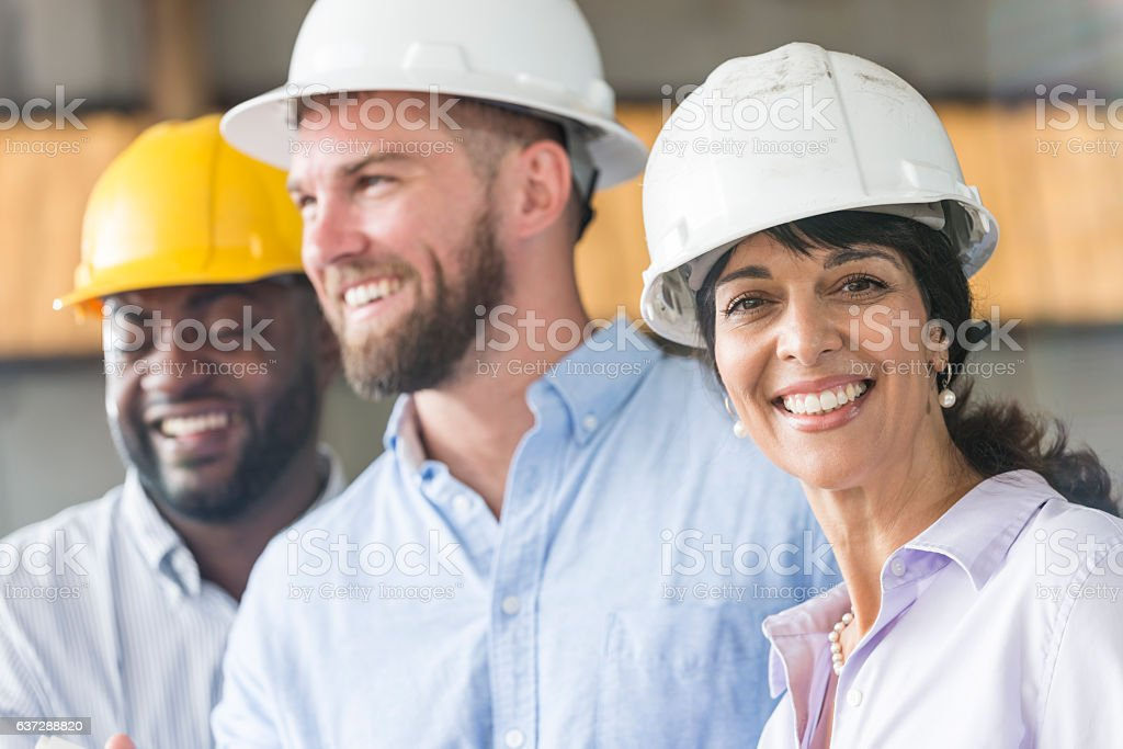 Hispanic woman with group of workers in hardhats stock photo
