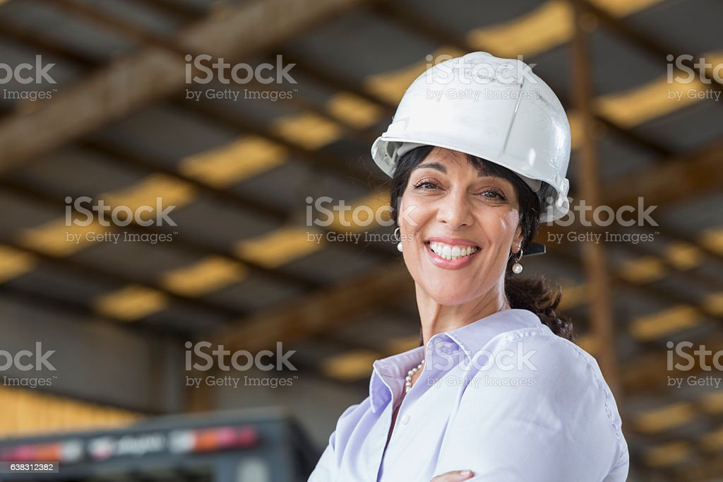 Hispanic woman with hardhat working in warehouse stock photo