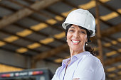 Hispanic woman with hardhat working in warehouse