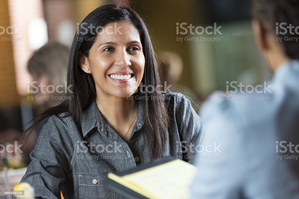 Hispanic woman with resume applying for job during interview meeting stock photo
