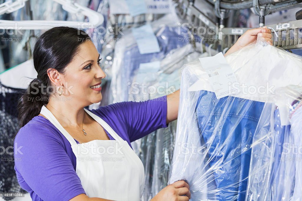 Hispanic woman working in dry cleaners stock photo